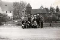 Zdjęcie dzieci ze Swornegaci na tle drewnianej świątyni znajdującej się obecnie we Wdzydzach Kiszewskich